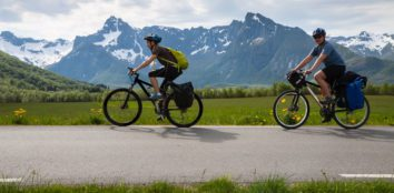 two mountain bikes being ridden on the road