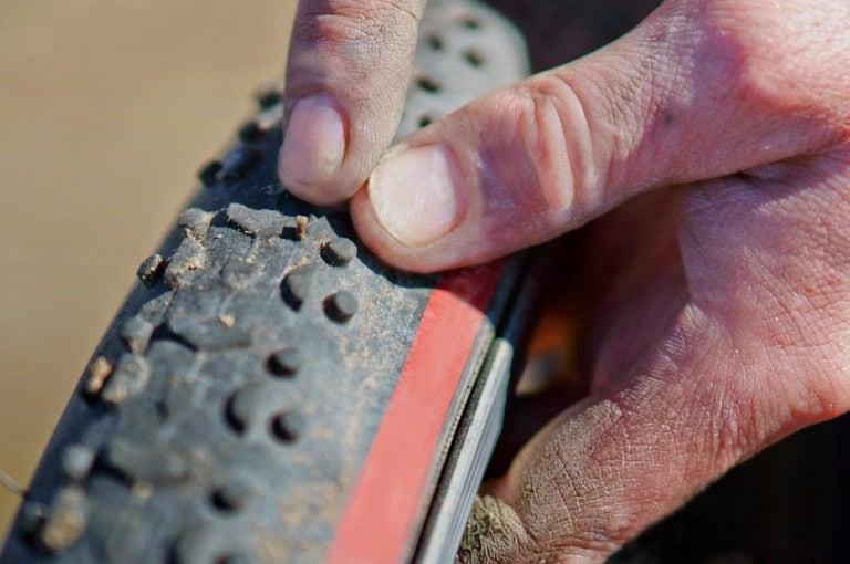 man checking his road bike tyres