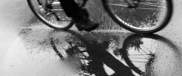 man riding his electric bike in the rain