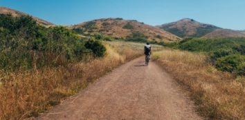 man riding his hybrid bike down the dirt trails