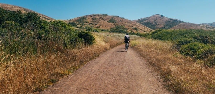 man riding his hybrid bike down the dirt trails