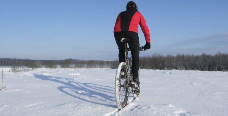 man riding mountain bike through the snow