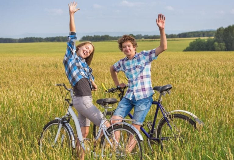two kids riding hybrid bikes off road
