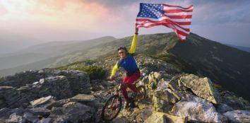man on a maountain bike holding a usa flag