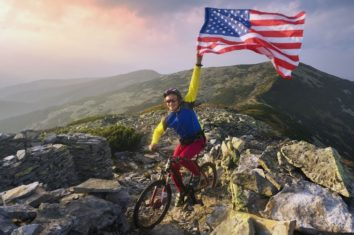 man on a maountain bike holding a usa flag
