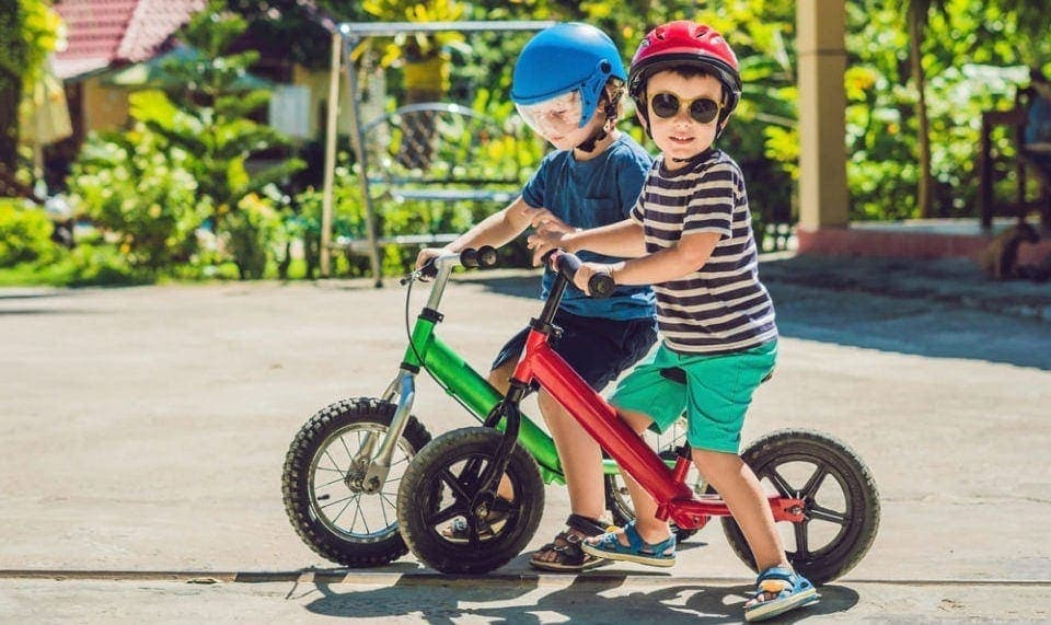 two kids riding on balance bikes