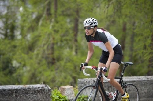 a woman riding her road bike uphill