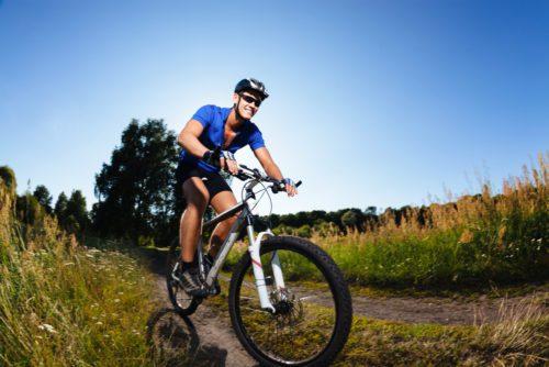 cyclist riding mountain bike through dirt trails