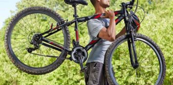 a man carrying his mountain bike on his shoulder