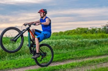 a man doing the wheelie trick with a mountain bike