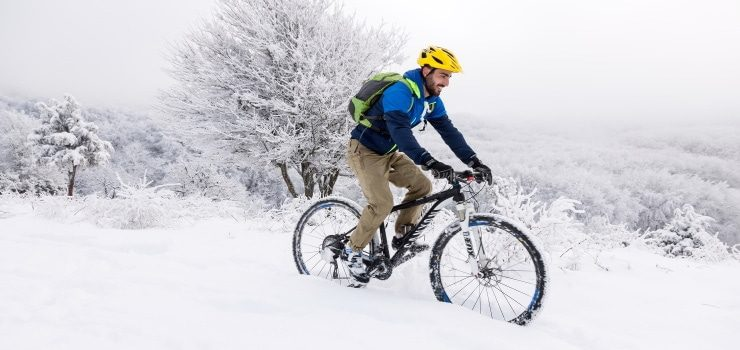 a man having fun riding his mountain bike in the snow
