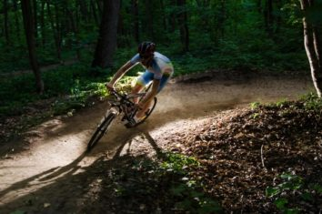 a man on his mountain bike taking a curve in the forest