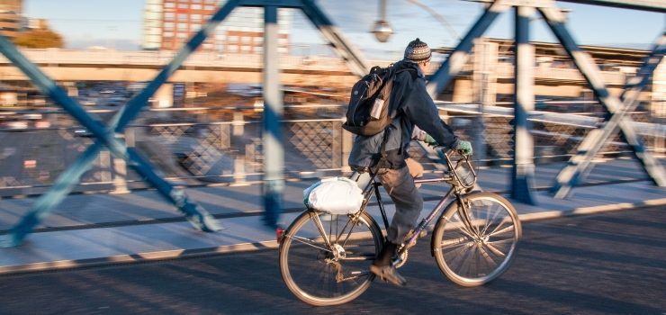 a man riding a hybrid bicycle through the city