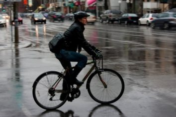a man riding his bicycle in the city on a rainy day