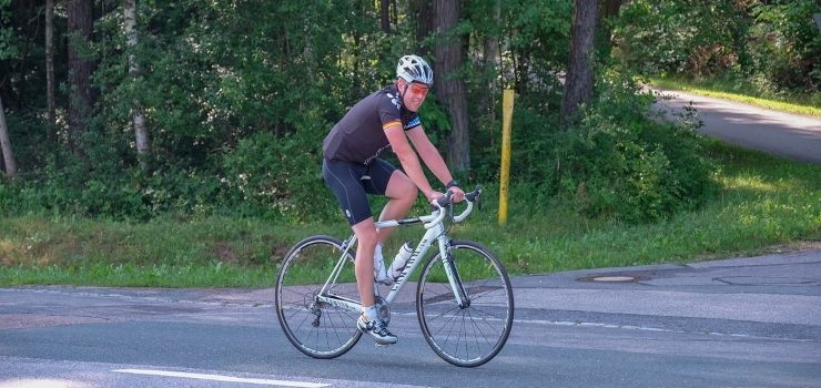 a man riding his bicycle on the road