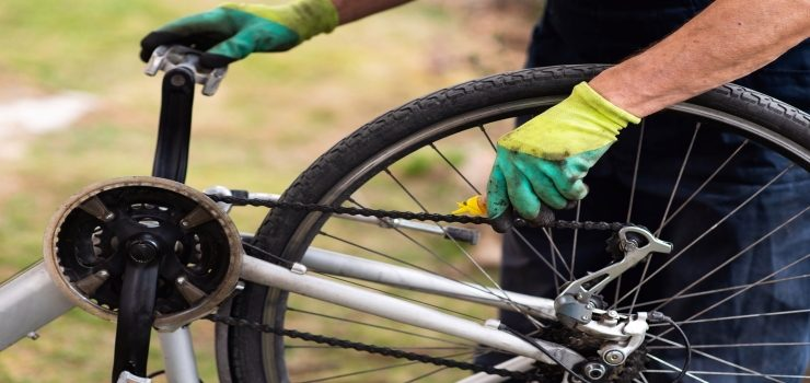 a person lubricating his bicycle chain