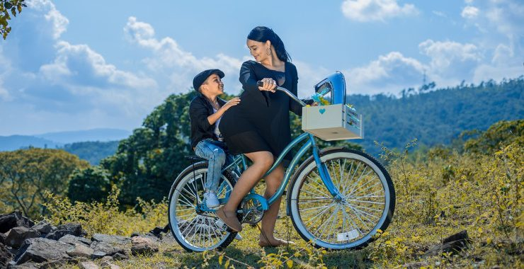 a pregnant woman riding a bicycle with her son