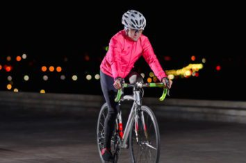 a woman riding her bicycle at night