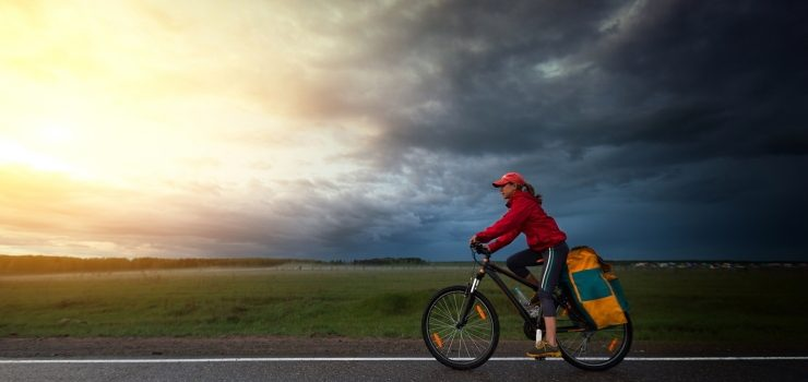 a woman riding her bicycle under a cloudy sky