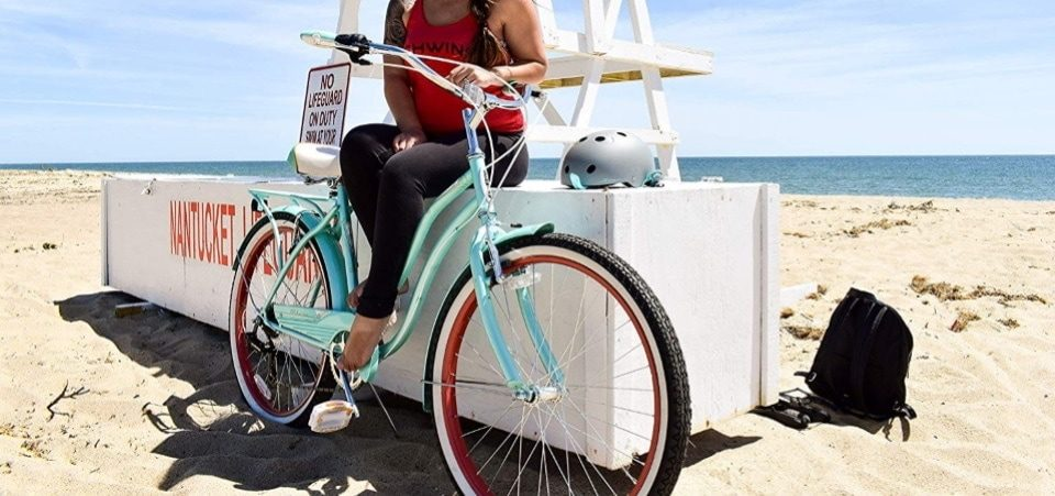 a woman sitting near her hybrid bike on the beach