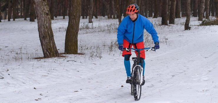 cyclist riding mountain bike in the winter forest