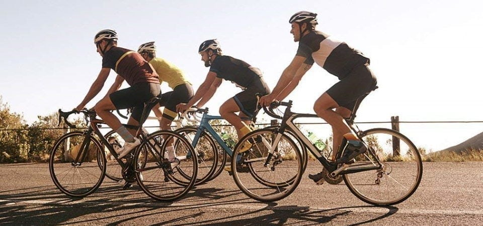 four men riding their bicycles on the road
