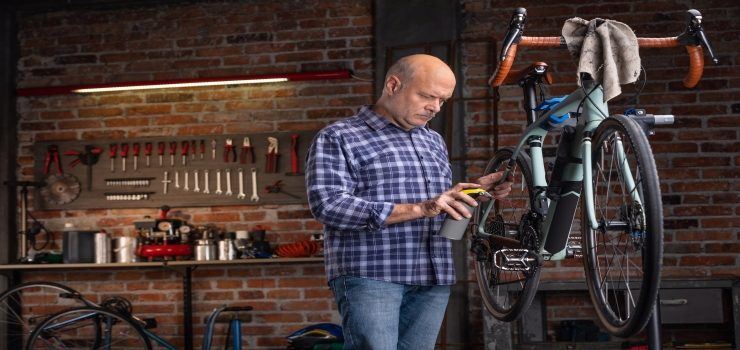 man oiling the chain on a bicycle in a workshop