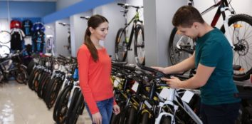man showing bicycle to woman in store