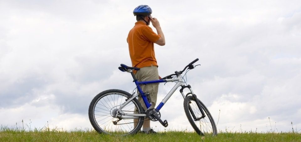 man with a mountain bike in a meadow talking on a mobile phone