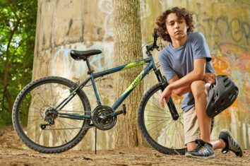 the boy is kneeling and his mountain bike is behind him