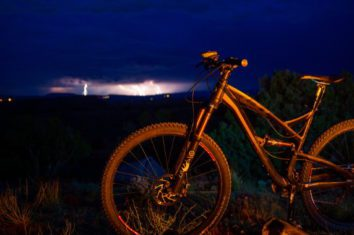 a mountain bike standing while a lightning storm is seen in the background