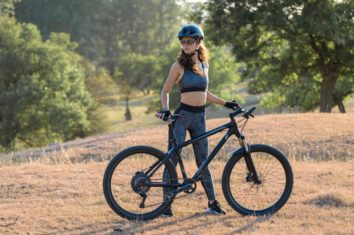 the woman is standing next to her mountain bike