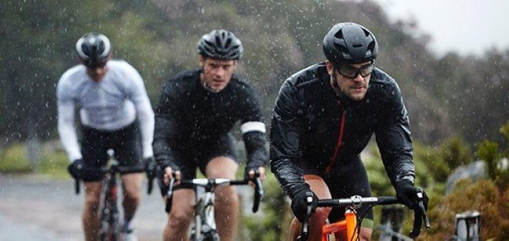 three man riding their bikes in the rain