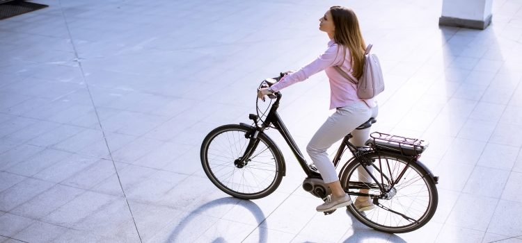 young woman with city electric e-bike